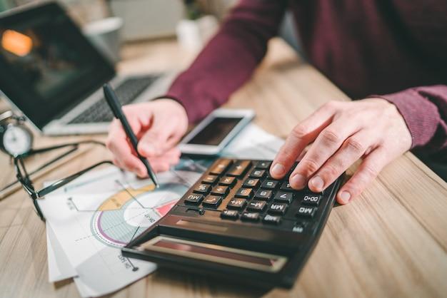 Mannelijke accountant thuis werken berekeningen maken