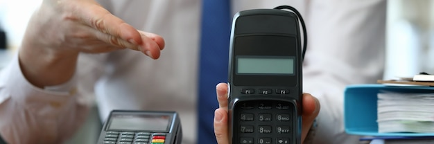 Mannelijke adviseur demonstreert betaalterminal voor plastic kaarten
