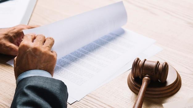 Mannelijke advocaat die de documenten in een rechtszaal op houten bureau draait