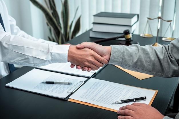 Mannelijke advocaat die de hand schudt met de cliënt na een goede samenwerkingsbijeenkomst voor onderhandeling in de rechtszaal.