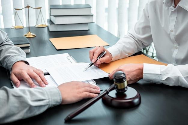 Mannelijke advocaat die onderhandelingszaak bespreekt met cliëntvergadering met documentcontact in rechtszaal, recht en rechtvaardigheidsconcept.