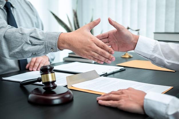Mannelijke advocaat handen schudden met cliënt na goede deal onderhandeling samenwerking bijeenkomst in rechtszaal