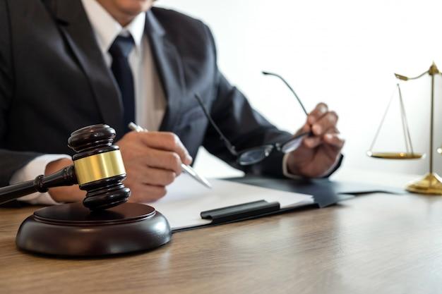 Mannelijke advocaat of notaris die aan documenten en rapport van de belangrijke zaak in het advocatenkantoor werkt