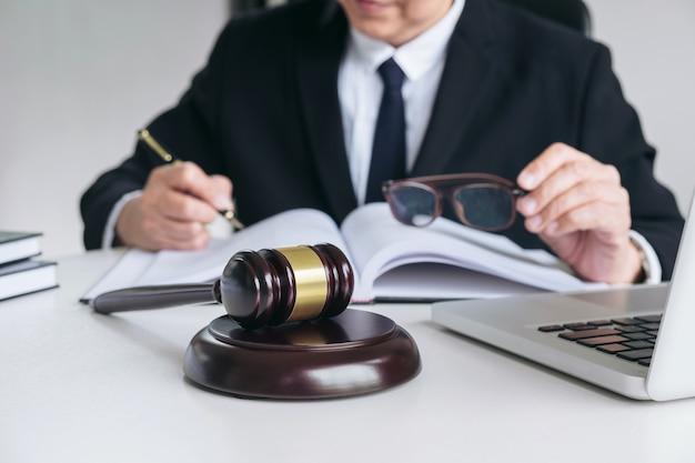 Mannelijke advocaat of rechter die met rechtsboeken werkt
