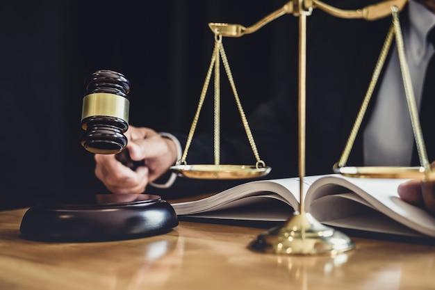 Mannelijke advocaat of rechter werken met contract papieren, wetboeken en houten hamer op tafel in rechtszaal, justitie advocaten bij advocatenkantoor, recht en juridische diensten concept