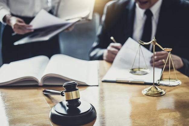 Mannelijke advocaten of raadgevers die in de rechtszaal werken, hebben een ontmoeting met de klant en overleg met contractpapier