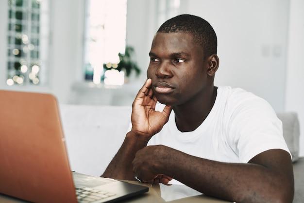 Mannelijke afrikaanse amerikaanse freelancer met laptop thuis
