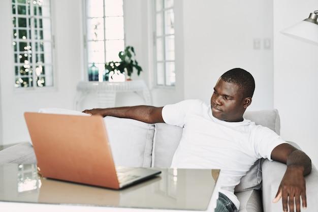 Mannelijke afro-amerikaanse freelancer met laptop thuis