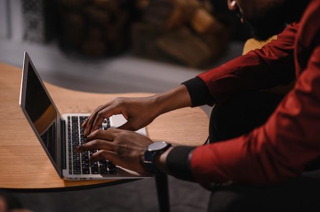 Mannelijke afro-amerikaanse gebruiker handen typen op laptop toetsenbord zitten aan tafel, student professionele studie werken met pc-softwaretechnologie concept, close-up.