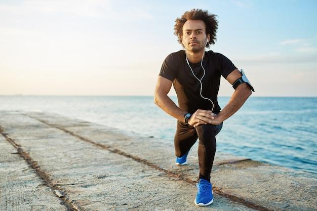 Mannelijke afro-amerikaanse jogger met borstelige kapsel warming-up zijn spieren voor het hardlopen. man atleet in zwarte sportkleding en blauwe sneakers benen strekken met rekoefening op pier.