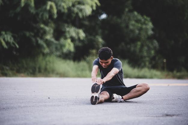 Mannelijke agent die uitrekkende oefening doet, die voor training voorbereidingen treft