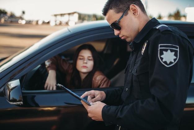 Mannelijke agent in uniform schrijft een boete uit aan vrouwelijke chauffeur