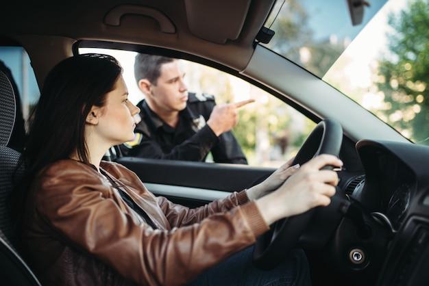 Mannelijke agent in uniform wijst de weg naar vrouwelijke chauffeur