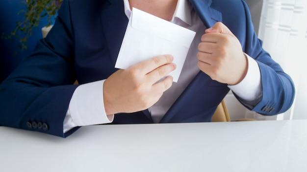 Mannelijke ambtenaar neemt steekpenningen in envelop en stopt deze in jas Premium Foto