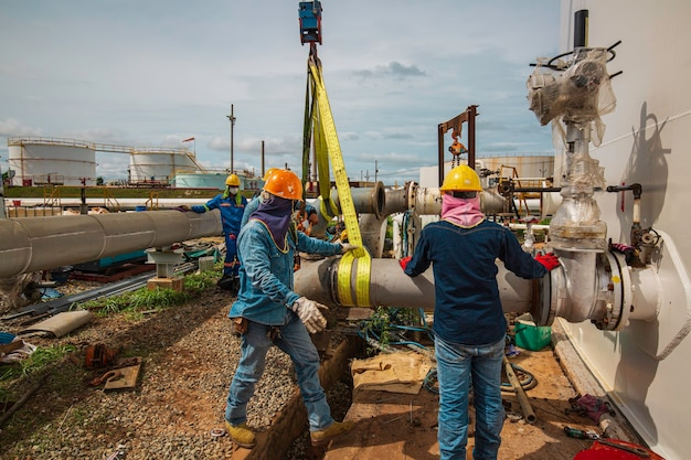 Mannelijke arbeider de slinger bij kraanwerk. lossen door de kraan van de olie- en klepapparatuur van de productiepijpleiding.