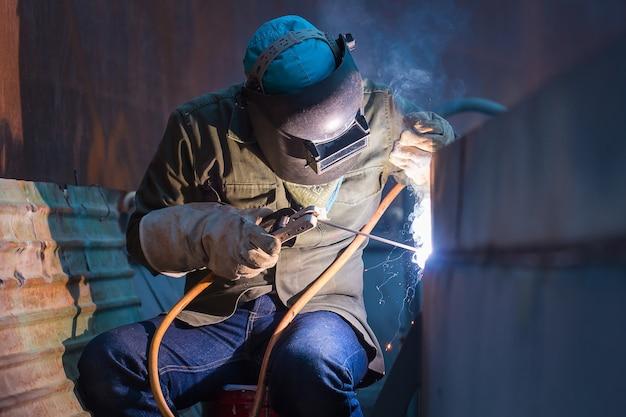 Mannelijke arbeider die beschermende kleding draagt en een plaattankolie voor het lassen van industriële constructie in besloten ruimtes.