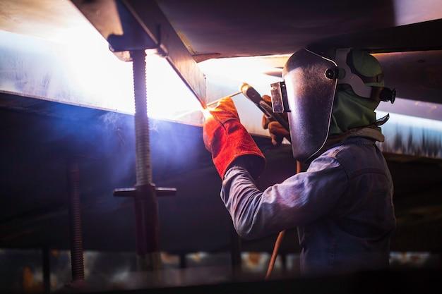 Mannelijke arbeider die beschermende kleding draagt en reparatielassen van industriële bouwolie en gas of opslagtank in besloten ruimten repareert.