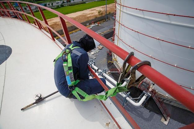 Mannelijke arbeider die veiligheidsharnas draagt en alleen werkt op een hoge leuning op open tankdakolie
