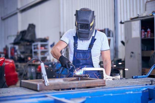 Mannelijke arbeider in lashelm die metaal in garage lassen