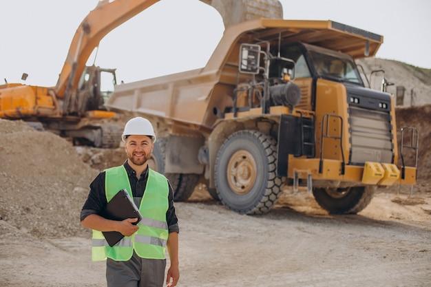 Mannelijke arbeider met bulldozer in zandgroeve