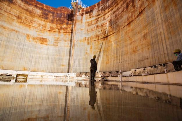 Mannelijke arbeider touw hijsplaat installatie van de binnenkant van de opslagtank met drijvend dakwater.