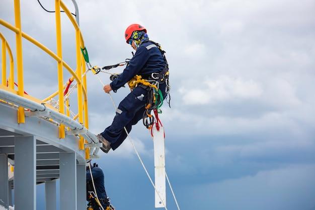 Mannelijke arbeiders controleren de kabeltoegangsinspectie van de kabel naar beneden op het dak van de tank van de opslagtank van de dikte van de schaal op hoogte.
