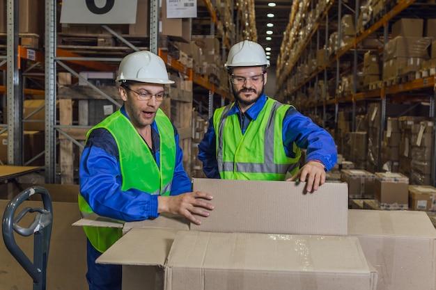 Mannelijke arbeiders die in dozen in magazijn kijken