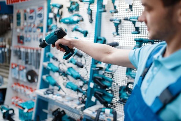 Mannelijke arbeidershand houdt elektrische boor vast in gereedschapswinkel
