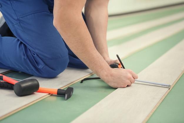 Mannelijke arbeidershanden die laminaatvloeren installeren