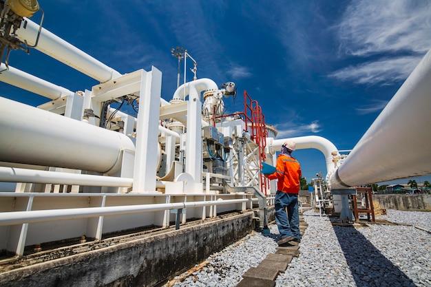 Mannelijke arbeidersinspectie bij stalen lange pijpen en pijpelleboog in de oliefabriek van het station tijdens de raffinaderijklep van de pijplijnolie- en gasindustrie met visuele controlerecord