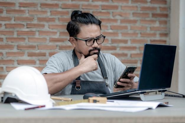 Mannelijke architect of ingenieur die thuis werkt en naar zijn telefoon kijkt