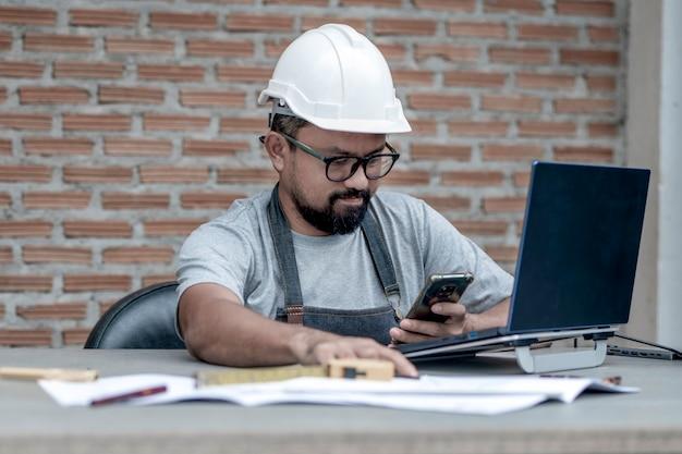Mannelijke architect of ingenieur met witte helm die thuis werkt en naar zijn telefoon kijkt