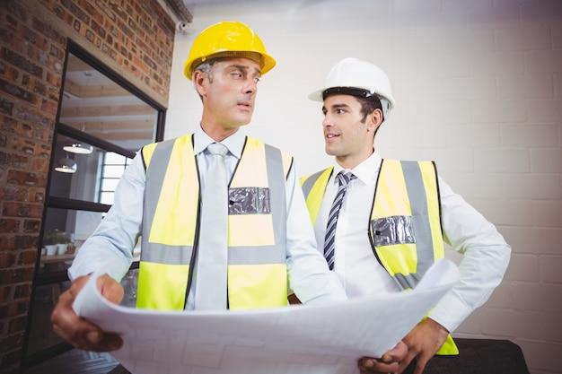 Mannelijke architecten bespreken terwijl blauwdruk