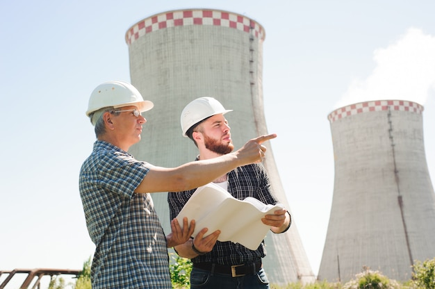 Mannelijke architecten die documenten samen herzien bij elektrische centrale.