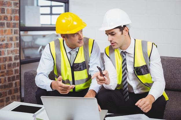 Mannelijke architecten die op laptop werken