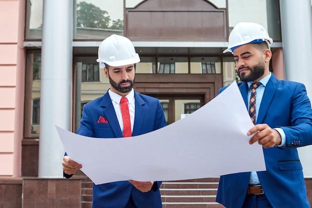 Mannelijke architecten met een blauwdruk