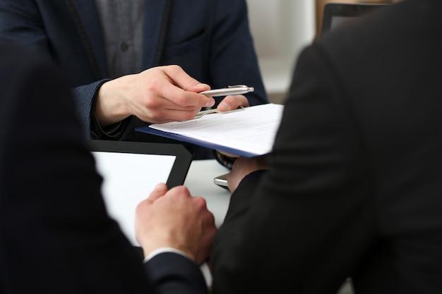 Mannelijke arm in pak biedt contractvorm op klembordkussen