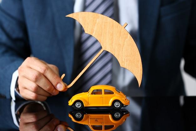 Mannelijke arm in pak en stropdas cover gele speelgoedauto