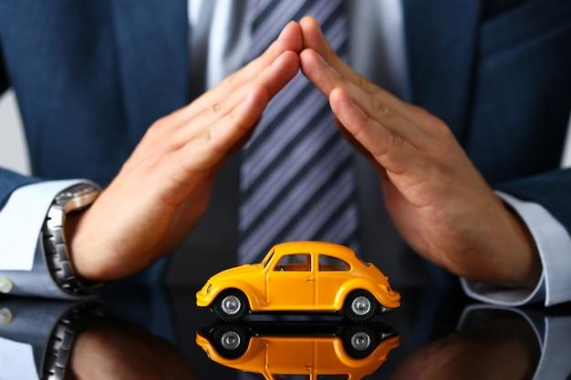 Mannelijke arm in pak en stropdas omslag gele speelgoedauto