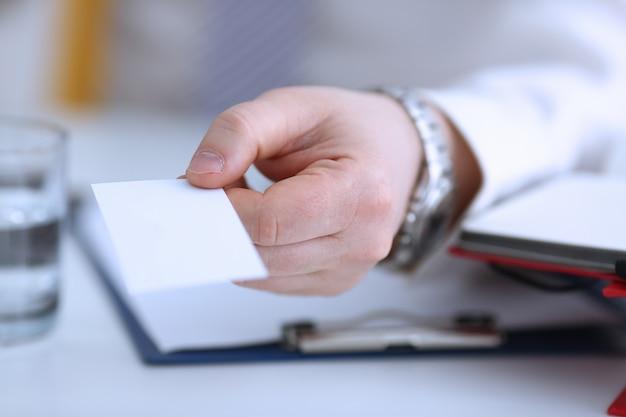 Mannelijke arm in pak geeft blanco visitekaartje aan bezoeker