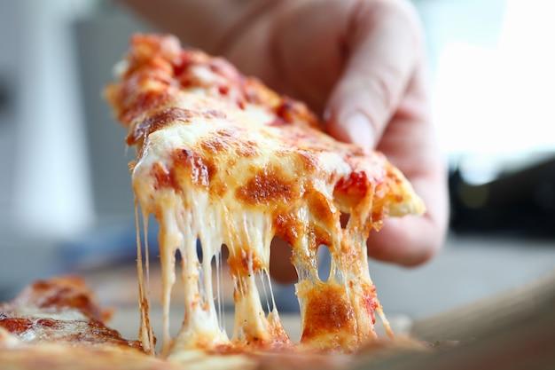 Mannelijke arm nemen plakje kaasachtige lekkere verse pizza