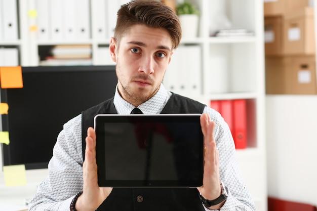 Mannelijke arm toont tablet pc-scherm naar cameraportret