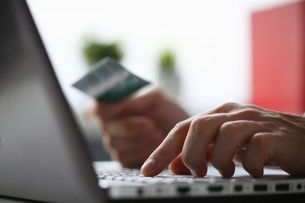 Mannelijke armen houden creditcard drukknoppen maken