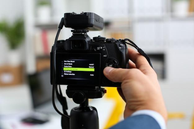 Mannelijke armen in pak mount camcorder op statief maken promo videoblog of fotosessie in kantoor close-up. vlogger past de instellingen aan en controleert de beeldkwaliteit om selfie-informatie over vacatures te tonen