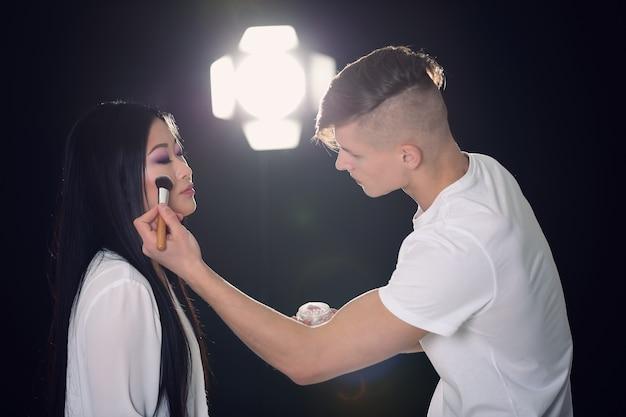 Mannelijke artiest die make-up doet voor model op donkere achtergrond