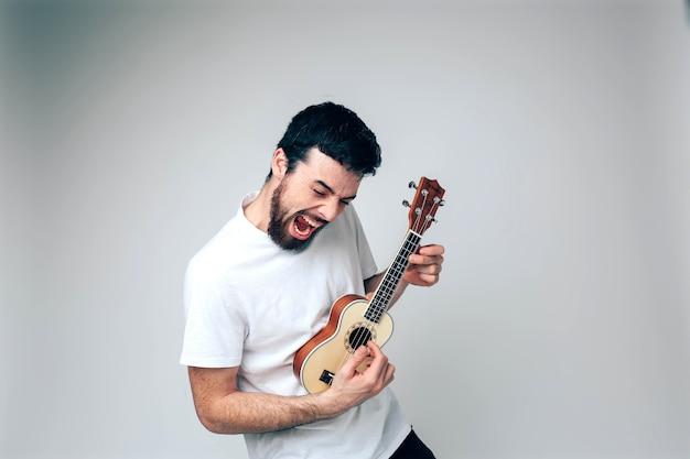Mannelijke artiest speelt op ukelele en zingt. hardop schreeuwen. oefenen in het spelen op kleine gitaar. veel plezier