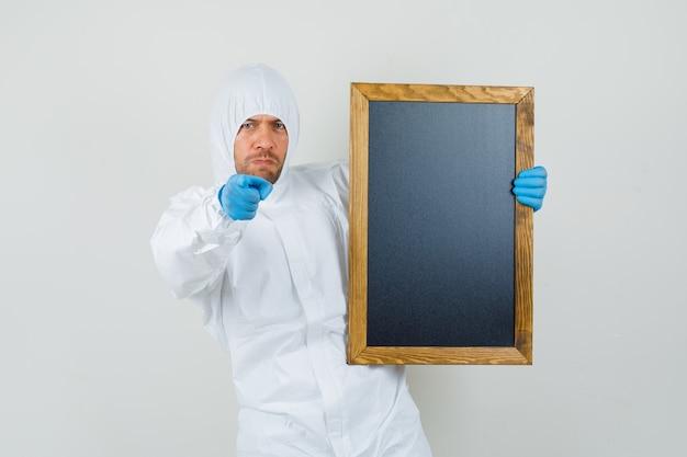 Mannelijke arts bedrijf schoolbord, wijzend op camera in beschermend pak