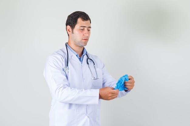 Mannelijke arts blauwe medische handschoenen in witte jas houden en voorzichtig kijken. vooraanzicht.