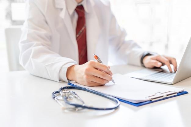Mannelijke arts die aan bureau met laptop werkt.