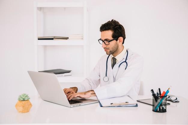 Mannelijke arts die aan laptop werkt